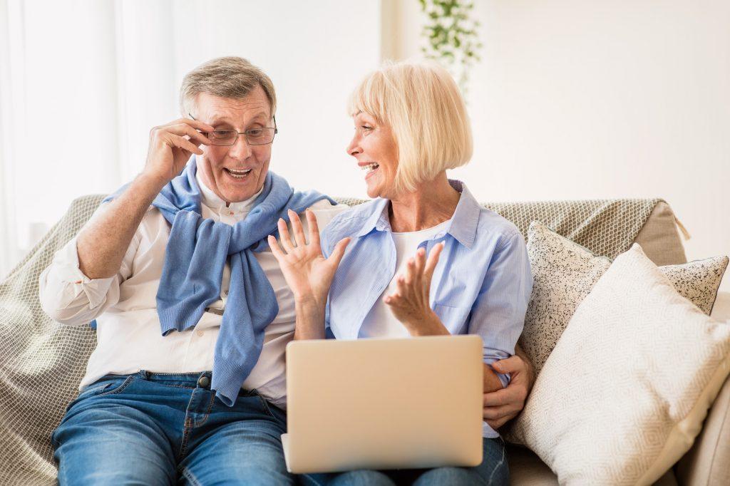 Surprised senior couple winning online auction bid on laptop